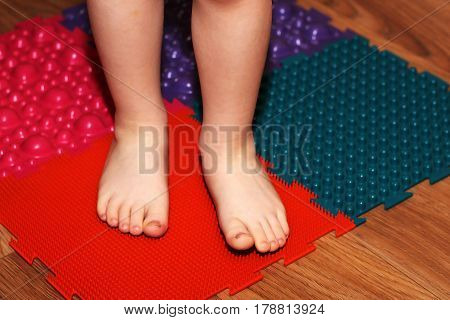 Children's feet on a massage mat. Treatment and health care.