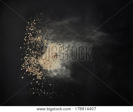 Top view of oat powder over black background