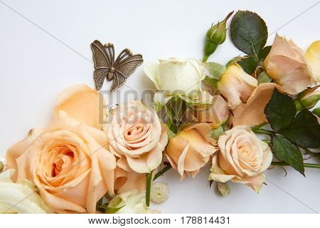 Close up of orange flowers with metal butterfly over white background