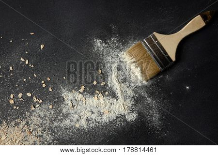 Top view of oat flakes and flour with brush over black background