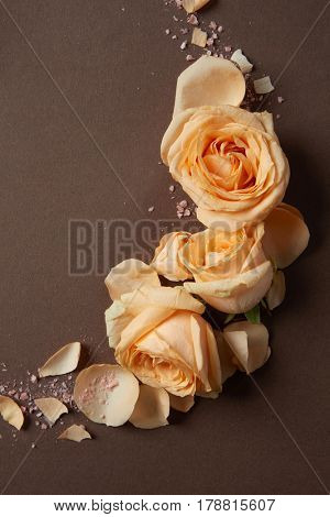 Decoration of orange flowers and petals over brown background