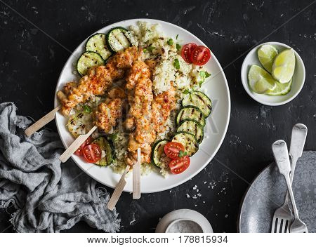 Chicken satay with cauliflower cous cous on a dark background top view. Flat lay