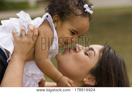 Hispanic mother hugging and kissing her daughter.