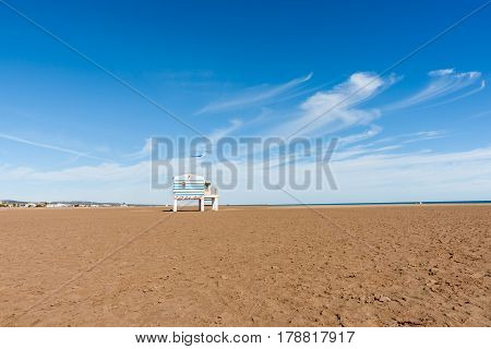 Gruissan, France - October 11, 2016; Wind blown cirrus cloud formations over wide dry sandy beach with beach hut on stilts and small insignificant unrecognisable people on horizon Mediterranean Beach at Gruissan France.