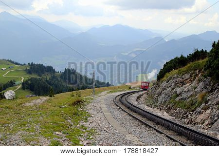 Travel To Sankt-wolfgang, Austria. The Railway With A Train With View On The Mountains And A Lake In
