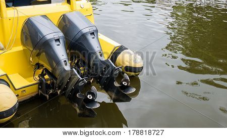 Close Up Of Two Motor Boat Engine Propellers Over Yellow Boat In Water. Boat Propellers Concept With
