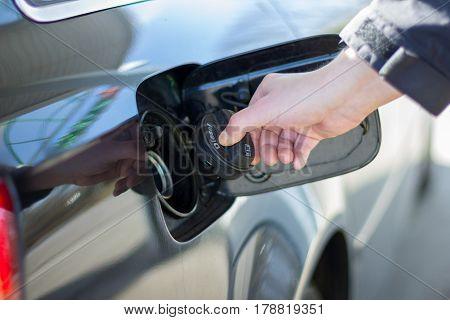 hand on a filler cap from a car