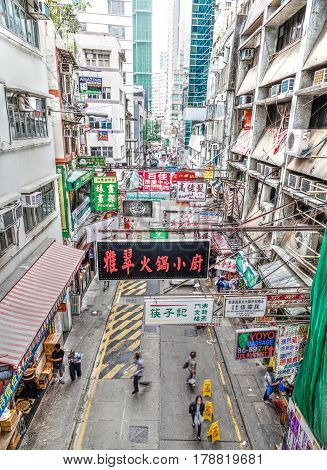 Hong Kong China - March 30 2015: Multiple street billboard ads hang on rafters along a busy street in the downtown Central District of Hong Kong Island. The area bustles with shoppers and tourists because of its many restaurants and fashion boutiques.