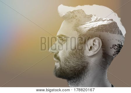 Profile of a handsome man against scenic view of snow covered mountains