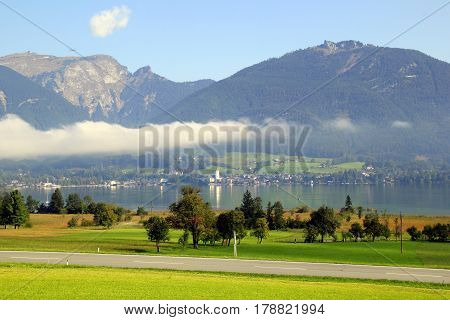 Travel To Sankt-wolfgang, Austria. The Road Between Green Meadows With The Mountains And A Lake In T