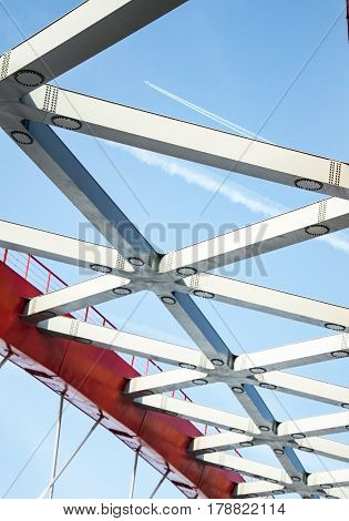 Airplane far in the sky, view from below through metal structures