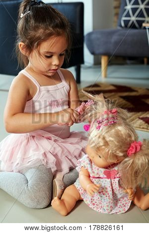 Cute little girl playing with doll at home on floor.