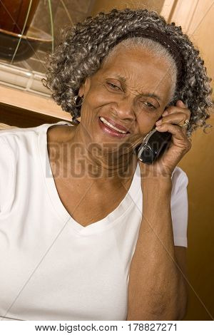 Elderly African American woman talking on the phone.