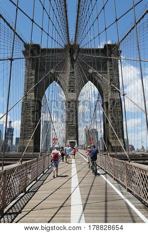 NEW YORK - JULY 19, 2016: Pedestrians and bicyclists crossing Brooklyn Bridge. About 4,000 pedestrians and 2,600 bicyclists cross the bridge every day.