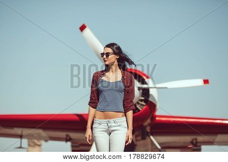 Pilot woman next to propeller plane outdoors in sunny day. Attractive young multi-racial Asian Caucasian sexy girl in jeans and shirt walking from sport airplane in airport.