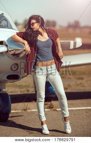 Pilot woman next to propeller of small private business plane outdoors in sunny day. Attractive young multi-racial Asian Caucasian sexy girl in jeans and shirt standing in full lenght at sport airplane in airport.