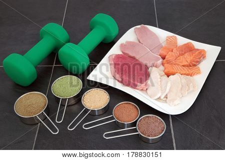 Body building high protein food of lean meat and salmon with supplement powders and dumbbell weights over slate background.