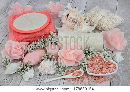 Spa beauty and body scrub cleansing products with himalayan salt, rose petal soap flowers, gypsophilia and  shells on distressed white wood background.