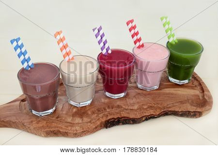 Health food supplement drinks of chocolate whey protein, maca root herb, acai berry, pomegranate fruit and wheat grass on an olive wood board. Also used by body builders.