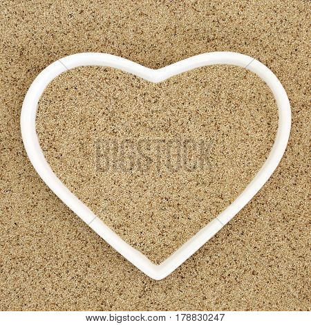 Teff super grain health food in a heart shaped porcelain dish and loose forming a background.