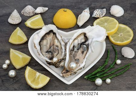 Oysters with pearls on a heart shaped plate with lemon fruit, samphire and shells on marble.