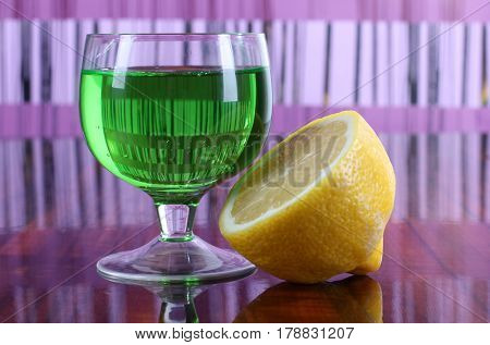 Glass cup with a cocktail and lemon on color background