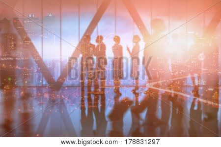 High angle view of illuminated cityscape against business colleagues having conversation in room