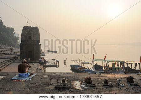 Maheshwar India - 3 February 2015: people doing yoga and meditation in front sacred river Narmada at Maheshwar on India
