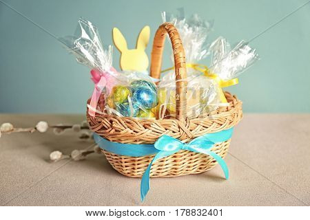 Easter basket with sweets and presents on light background