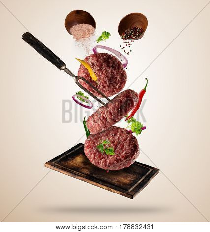 Flying raw milled hamburger meats pieces, with ingredients for cooking. Freeze motion. Fork holding the meat. Concept of food preparation in low gravity mode. Separated on smooth background