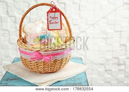 Easter basket with toy, cookies and greeting card on light background