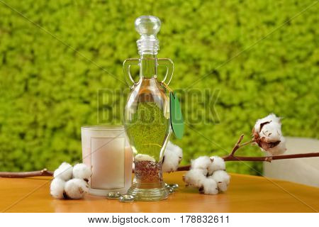 Bottle of essential oil and candle on wooden table against blurred background