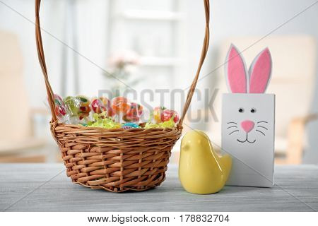 Traditional Easter basket with colorful treats, ceramic bird and gift bag on wooden table