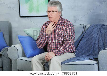 Sick senior man having pain in throat at home