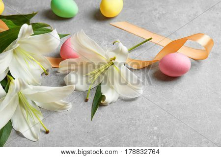 Beautiful lilies, eggs and ribbon on gray background