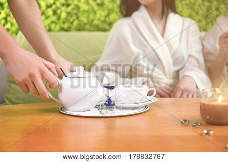 Hands of woman serving tea in spa salon and blurred clients on background