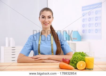 Young female nutritionist in her office