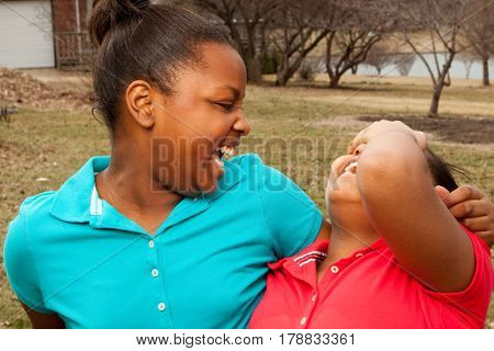 African American sisters and best friends smiling and laughing.