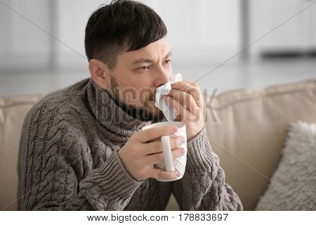 Young ill man drinking hot tea while sitting on sofa at home