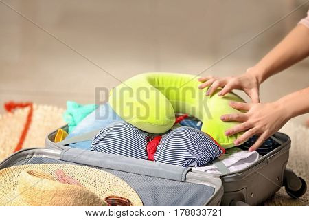 Hands of woman packing suitcase at home