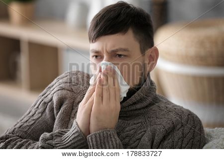 Young ill man blowing nose at home