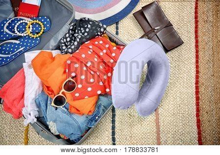 Open suitcase with different things and travel pillow on floor