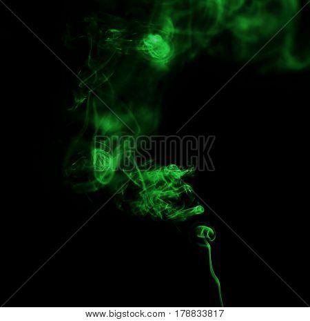 Swirl of green smoke on black background