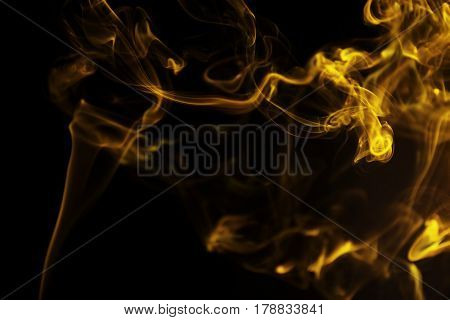 Swirl of yellow smoke on black background