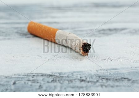 Cigarette butt on wooden background