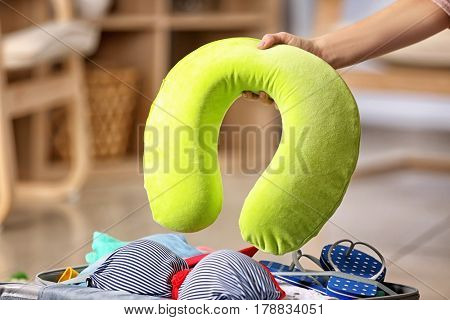 Hand of woman with travel pillow packing her suitcase at home