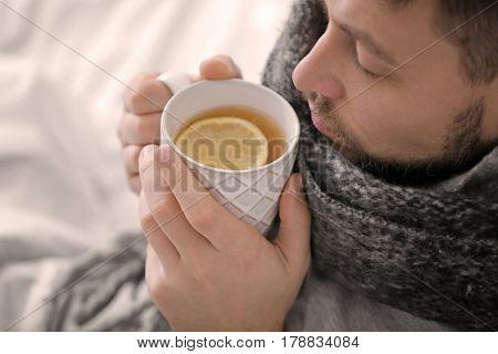 Young ill man drinking hot tea at home, closeup