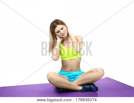 Young sporty woman suffering from neck pain on white background