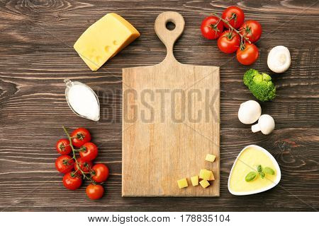 Still life with food ingredients and wooden board on table