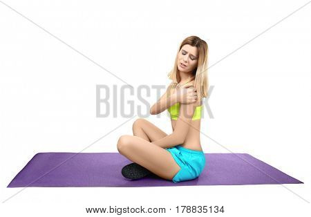 Young sporty woman suffering from pain in shoulder on white background